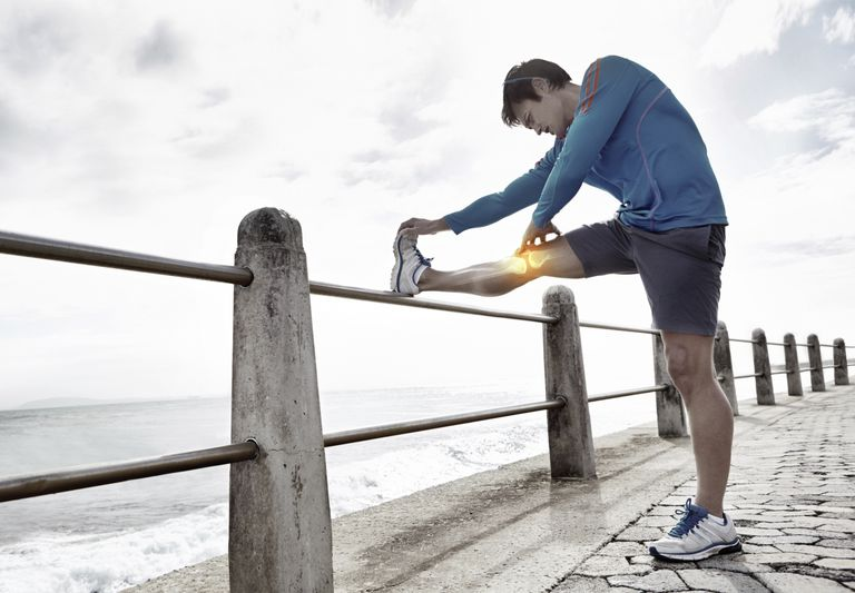 Man with inflamed knee stretching on pier