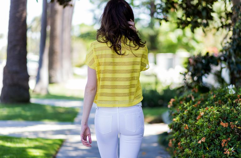 Woman wearing white jeans rear view