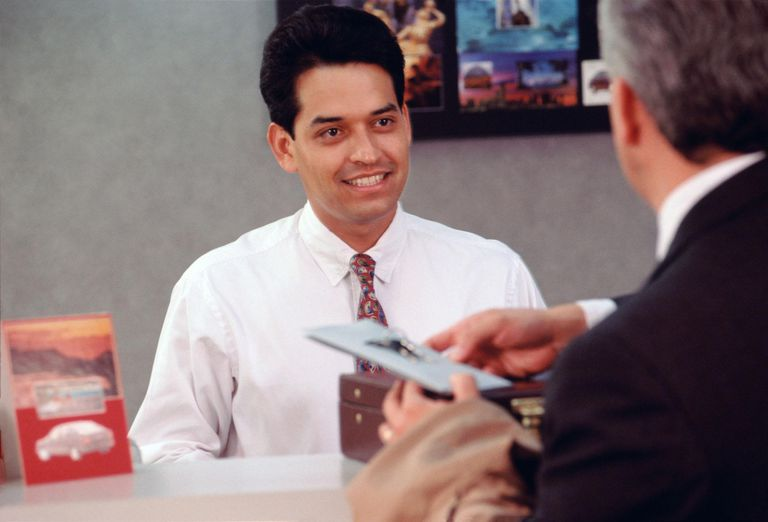 Mature man talking to salesman standing behind counter