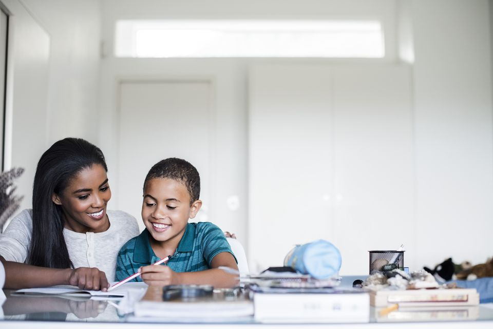 Mother assisting her son in doing homework