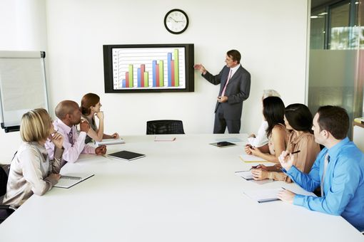 Group of people in a meeting looking at graph