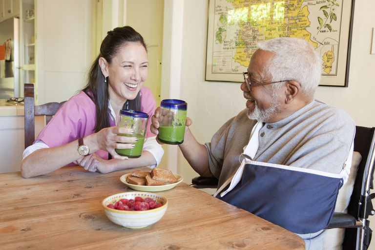 Caretaker and older man having smoothies