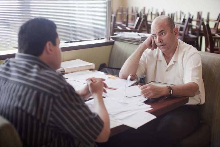 Coworkers having an intense conversation in a restaurant over paperwork