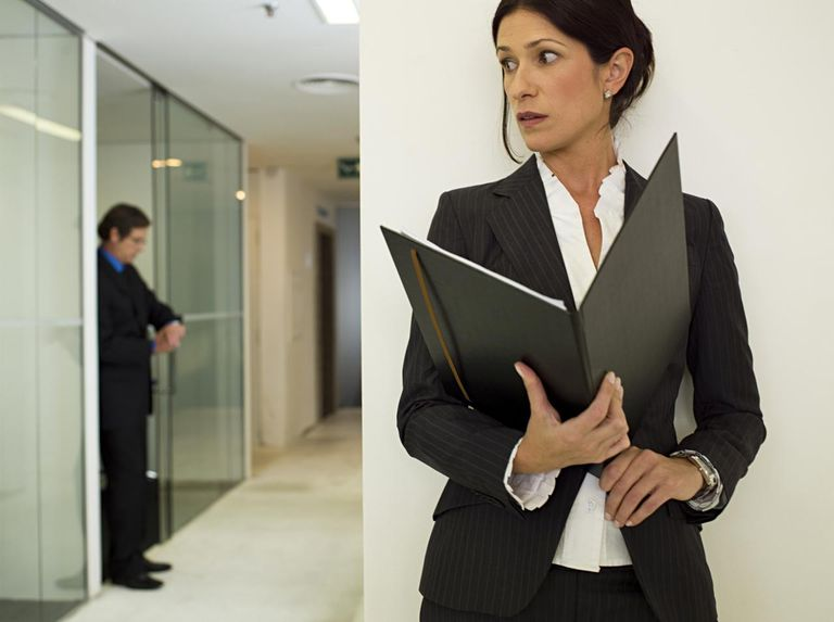 Businesswoman holding portfolio, man looking time in background