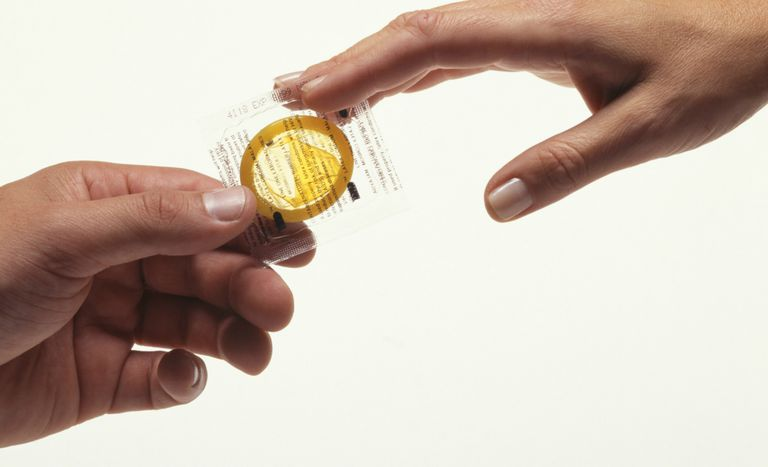 Man handing condom to woman