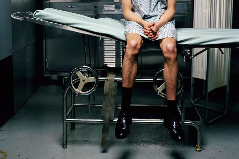 Mature male patient sitting on edge of examination table, looking down