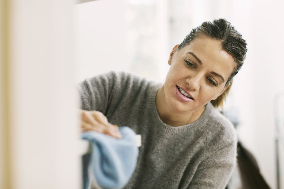 Woman cleaning shelf with rag