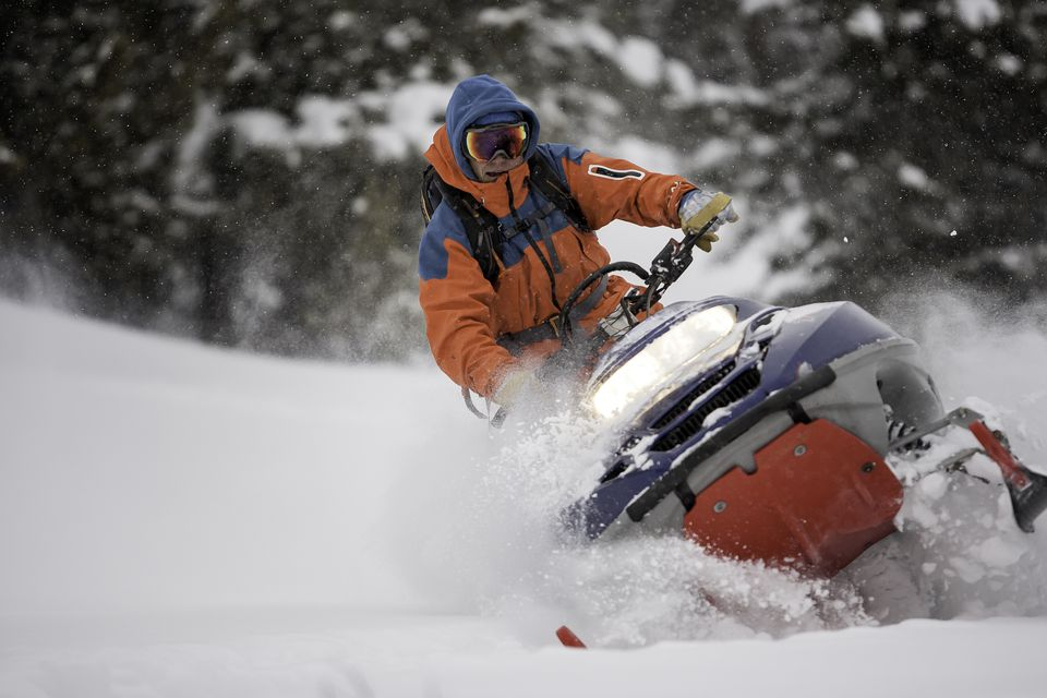 Guy on a snowmobile taking a powder turn.