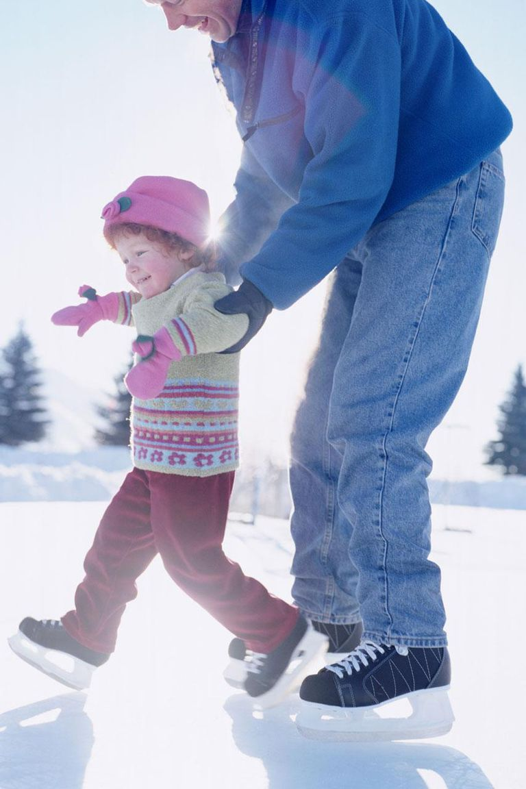 Father teaching daughter (2-4) how to ice skate, side view