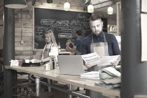 A coffee shop owner checks the delivery notes in his bookkeeping folder on the counter of his busy coffee shop and cross checks them with his online accountancy via his laptop. In the background two staff attend to the orders .