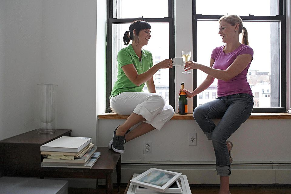 Roommates toasting new apartment with champagne