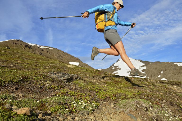 Female hiker jumping downhill