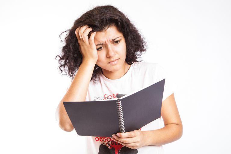 teenage girl looking confused at notebook