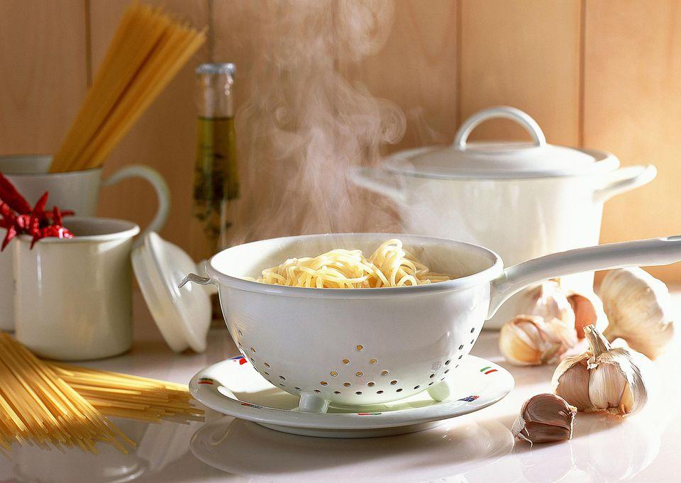 spaghetti in strainer on countertop