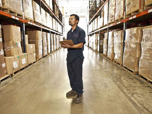 Man working in warehouse tracking inventory