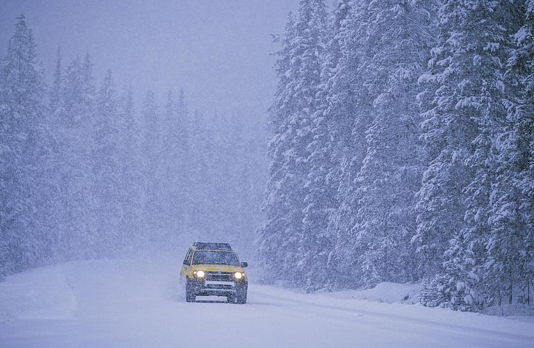 An SUV charges through the snow in a storm