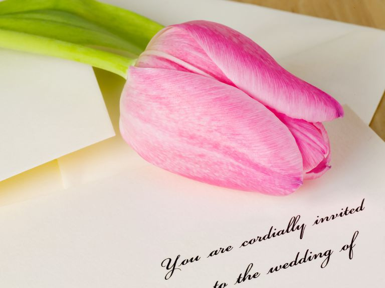 tulip resting on wedding invitation