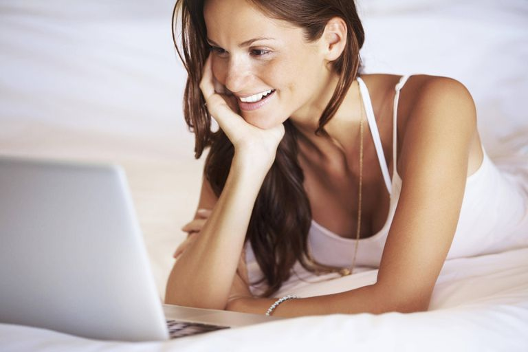 Woman using laptop while lying in bed