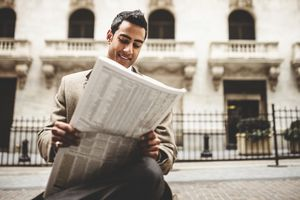 Business man reading a newspaper sitting on wall street
