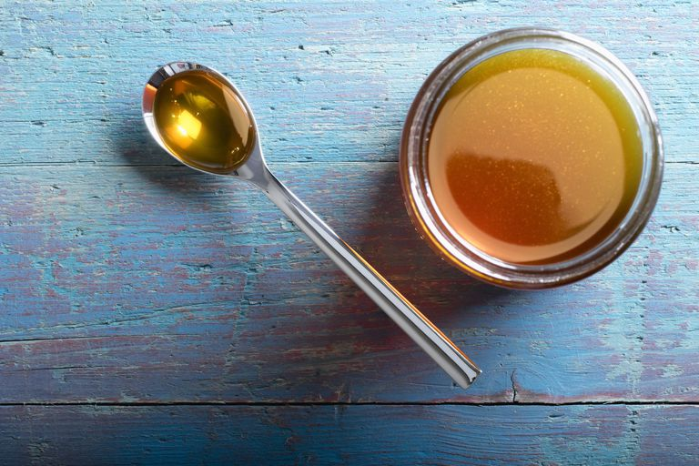Jar of golden honey with spoon on wooden table