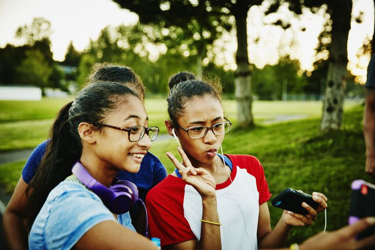 Sisters hanging out and taking selfies at park