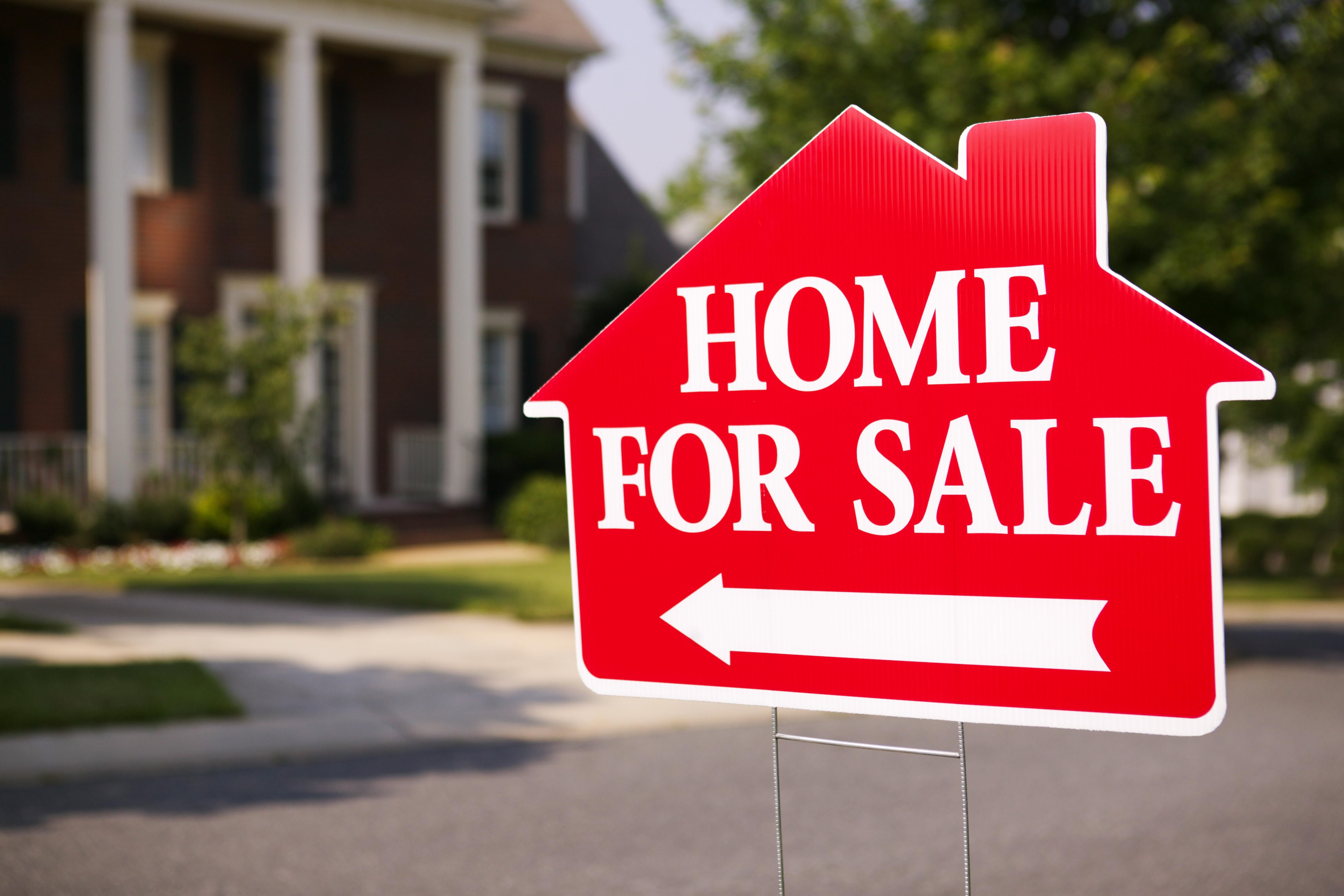 How to start flipping houses with bad credit - Close Up Of A Sign Pointing To A Home For Sale In Suburbia