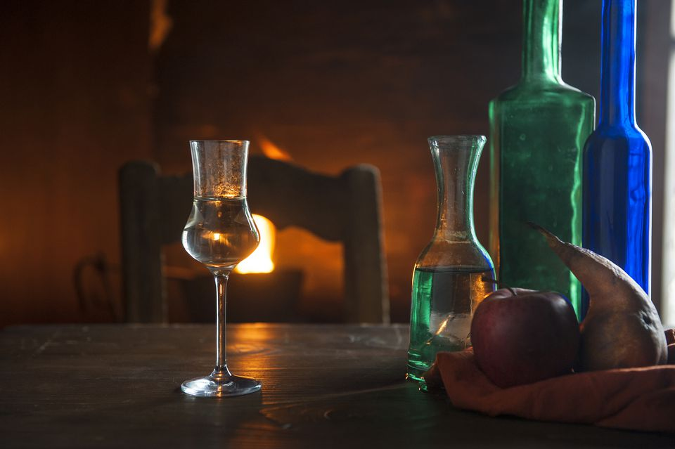 Shot glass and bottles in front of open fire