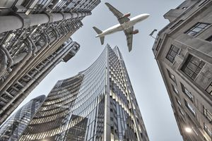 Jet plane flying low over Three different kind of architecture