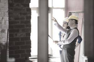 Male and female architects checking blueprint at construction site