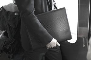 Businessman holding portfolio on train, mid section