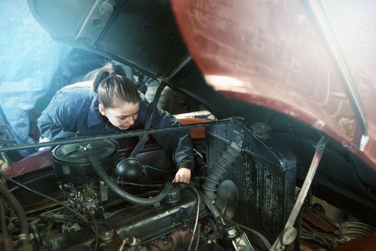 Female motor mechanic working on a car engine.