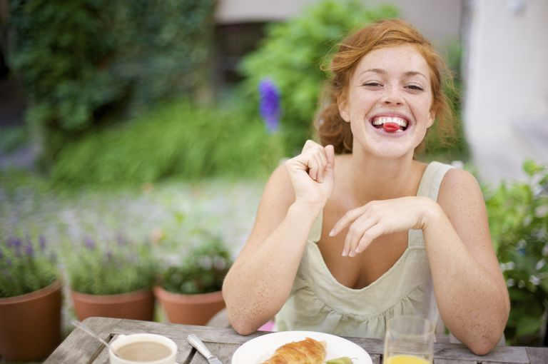 smiling woman eating breakfast