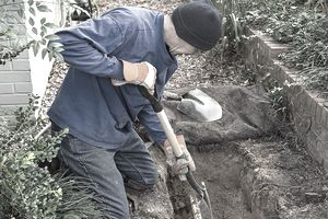 man digging next to house to check sewer line
