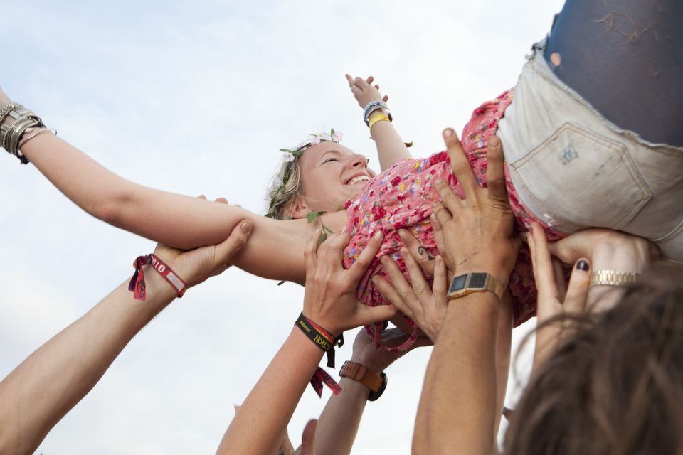 A girl crowd surfs with the help of her friends
