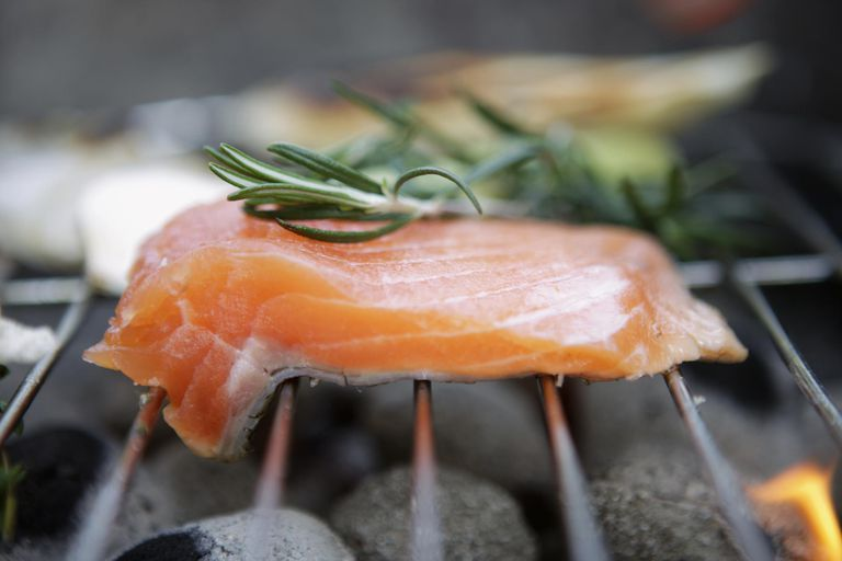 Salmon fillet with rosemary on grill, close-up