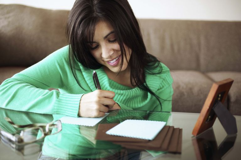 Woman writing thank you notes on coffee table