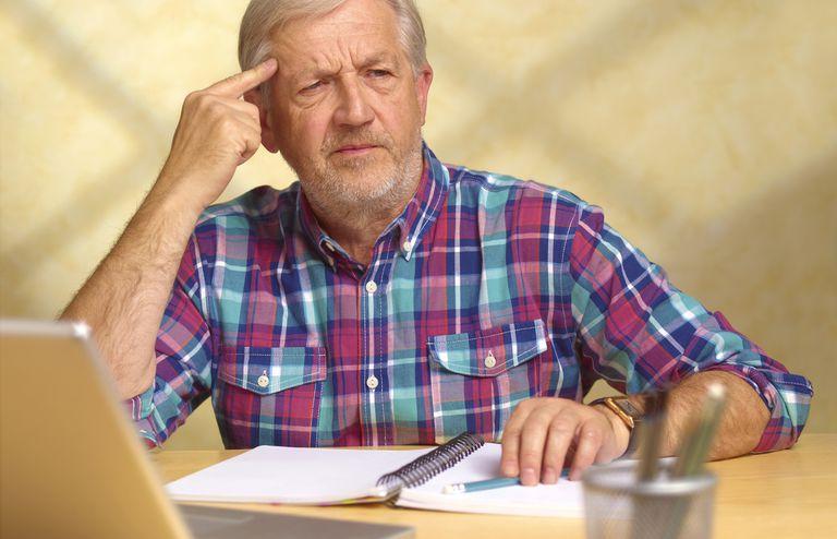 Older man thinking at computer.