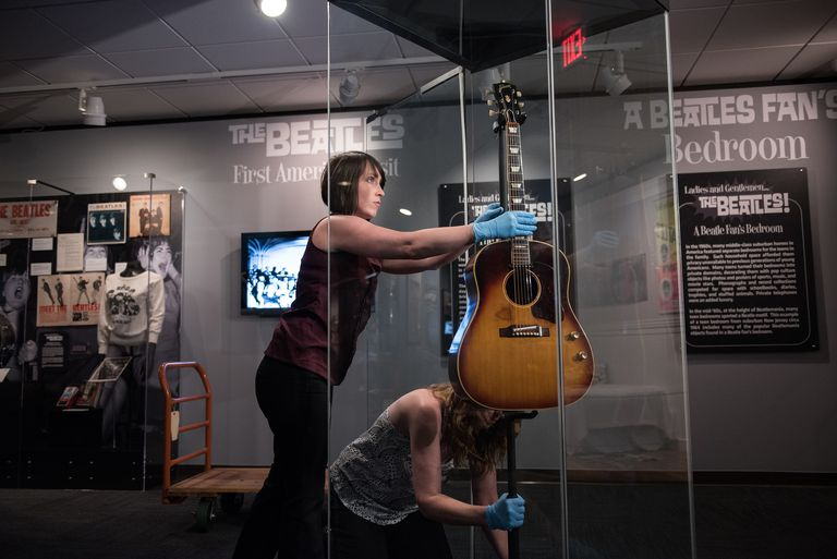 """Museum staff install John Lennon's Gibson J-160E guitar in the traveling exhibit """"Ladies and Gentlemen...The Beatles!"""""""
