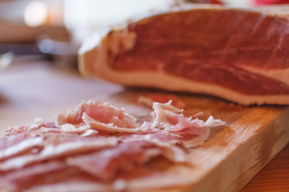 Close-up of cured ham on chopping board