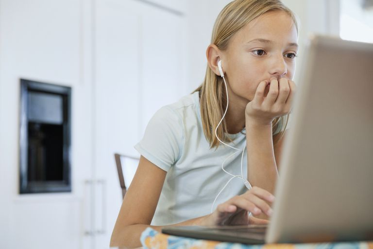 Girl using laptop while listening to music at table