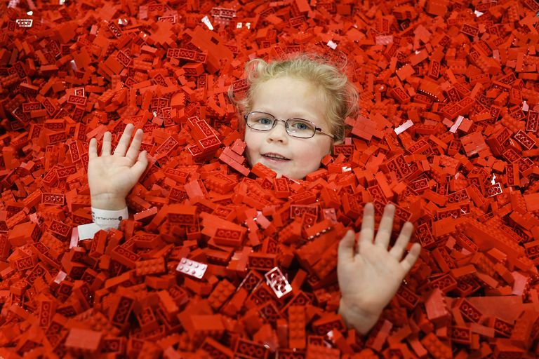 a hands and face of a child with glasses sticks out of a sea of red LEGO bricks