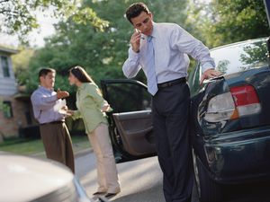 Businessman talking on his cell phone by a car accident