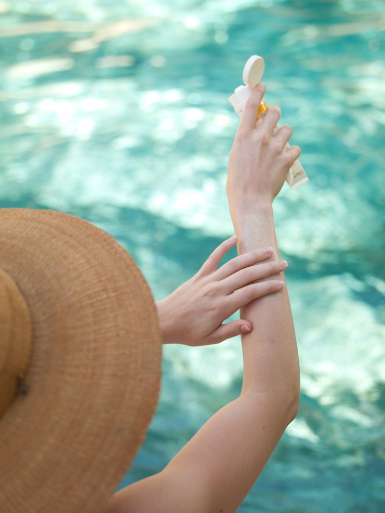 woman applying sunscreen next to pool