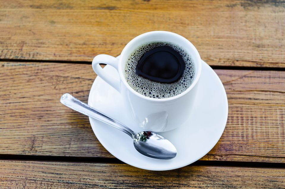 High Angle View Of Black Coffee On Wooden Table