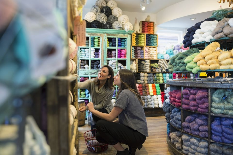 Yarn store owner helping customer