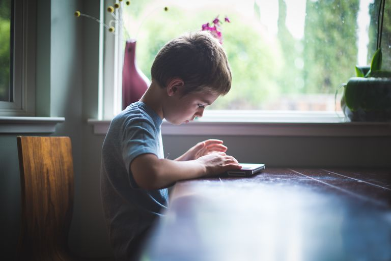 Kid playing with a tablet.