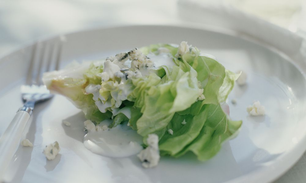 Blue cheese dressing and lettuce on a white plate.