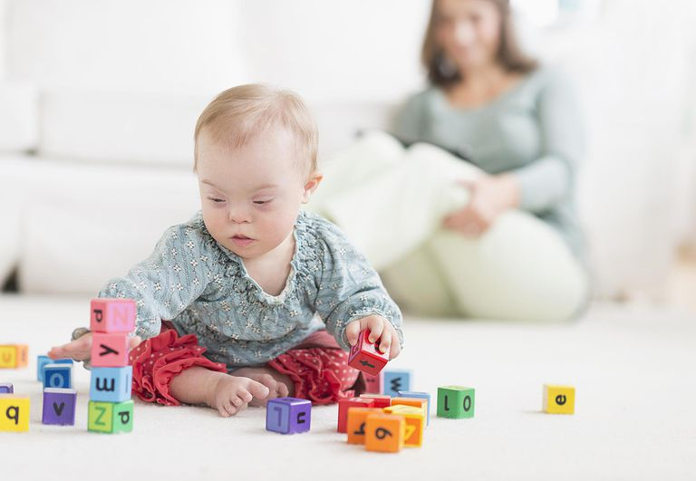Caucasian baby girl with Down Syndrome playing with blocks