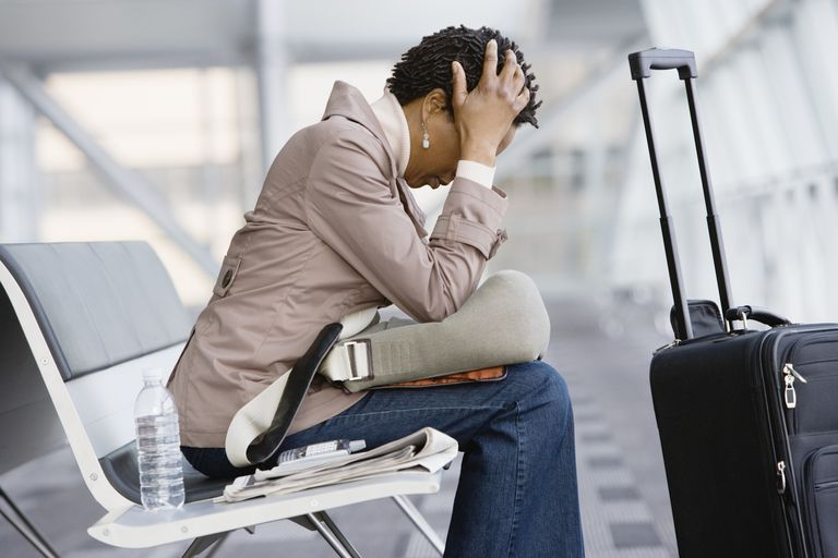 Woman with head in hands sitting on airport bench