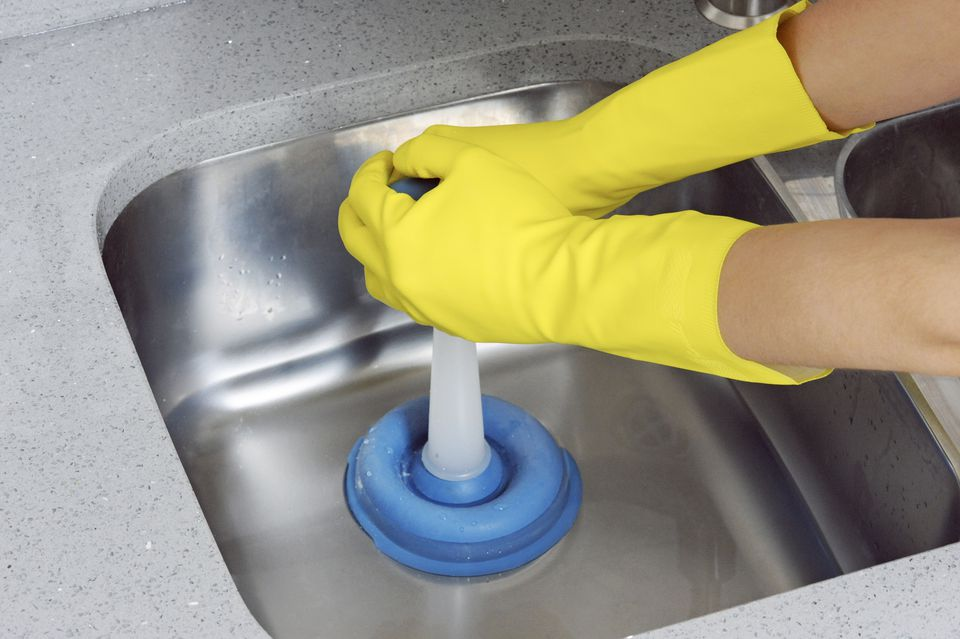 Woman wearing yellow dish gloves to unblock sink using plunger, close-up